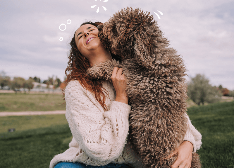 A very fluffy dog kissing a woman in a field